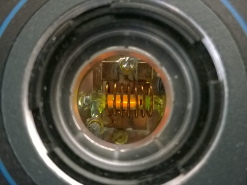 A europium-doped YSO crystal, of about 1 cm in length, as visibile from a window of our cryostat, while our yellow laser shines through it. The coil enveloping the crystal is used to address the spin states of europium via an oscillating magnetic field.
